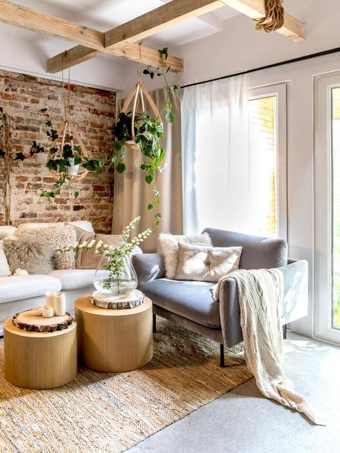 Salon w stylu rustykalnym z ceglaną ścianą, szarą sofą oraz stolikami pomocniczymi