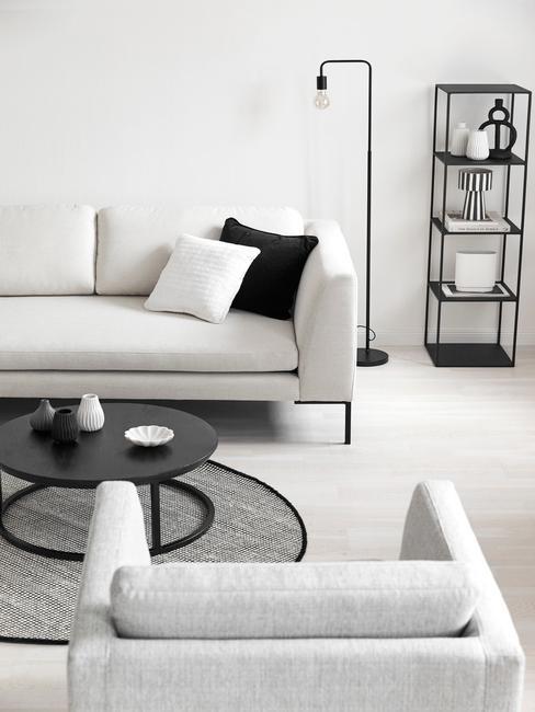 Industrialny salon z białą sofą i fotelem oraz czarną, metalową półką z dekoracjami