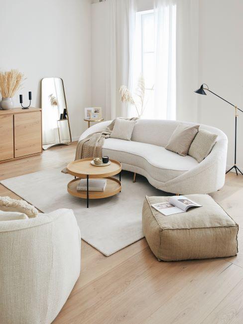 Jasny salon z białą, zaogrągloną sofa, krzesłem, beżowym pufem i okrągłym stolikiem kawowym