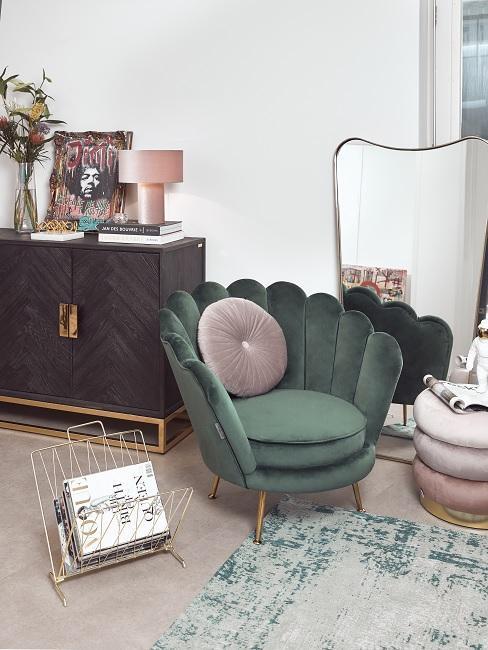 Salon z fotelem muszelką, drewnianą komodą oraz pufem