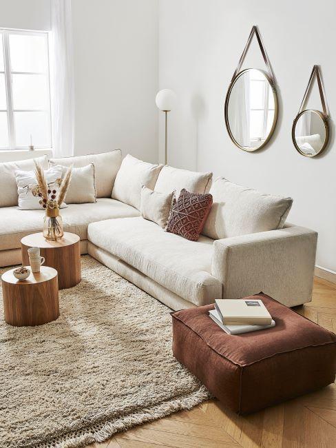 Salon z białą, narożną sofą, dywanem, drewnianymi stolikami oraz pufem