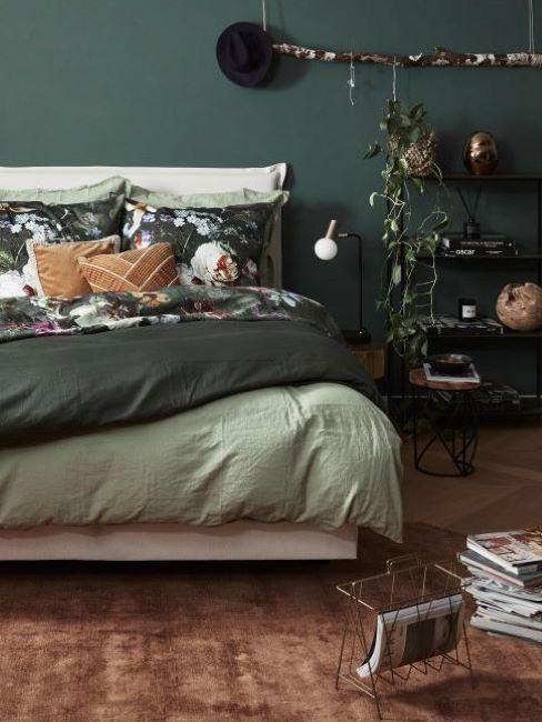 Sypialnia z zieloną ścianą, łóżkiem oraz rośliną