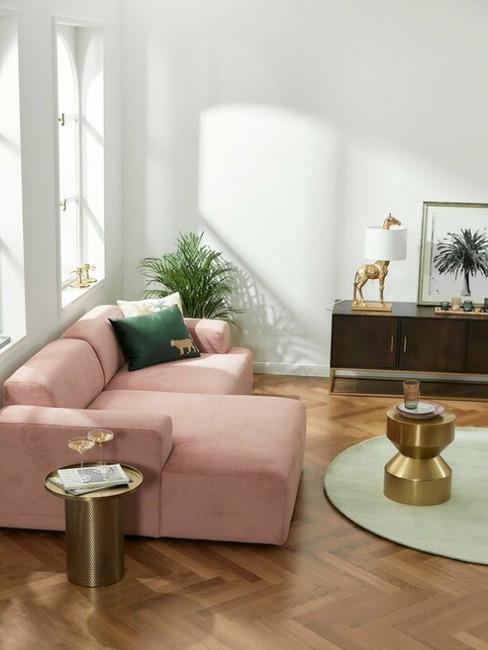 Jasny salon z różową, sztruksową sofą, stolikiem kawowym oraz komodą z drewna
