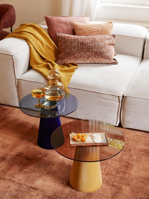 Zbliżenie na jasną sofę z kocem i poduszkami, dwa stoliki pomocnicze oraz dywan