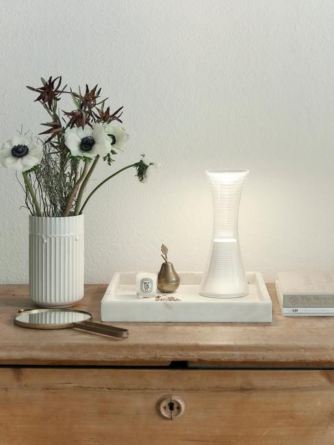 Zbliżenie na drewnianą komodę, na której znjduje się wazon z kwiatami i taca dekoracyjna