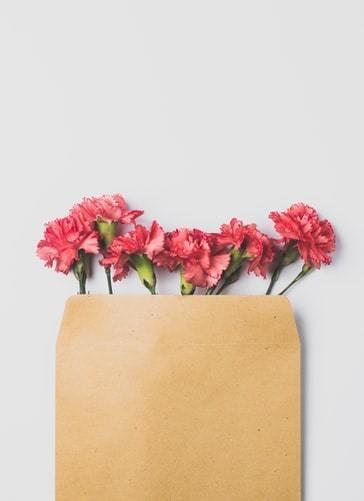 Brązowa koperta z różowymi goździkami na stole