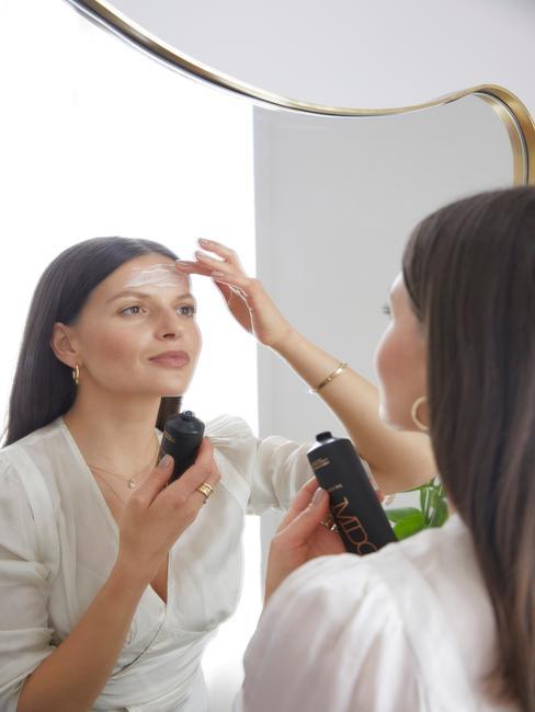 Kobieta stojąca przed lustrem i nakładająca na cerę kosmetyki