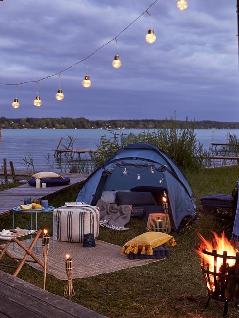Elegancko udekorowany namiot z powieszonymi lampkami i rozrzuconymi wokół poduszkami
