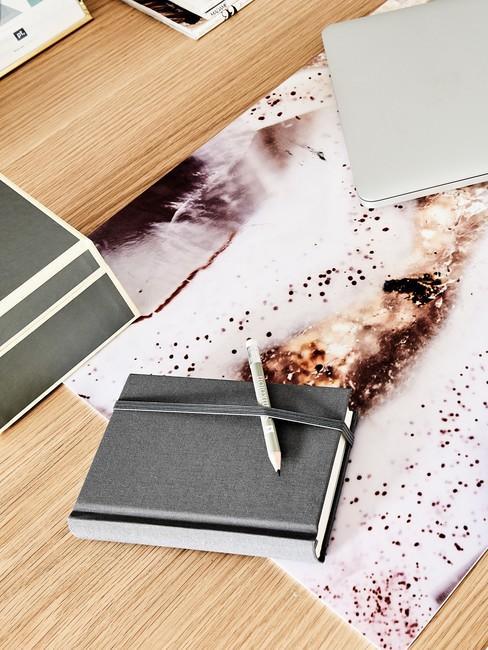 Czarny notes z długopisem leżący na biurku