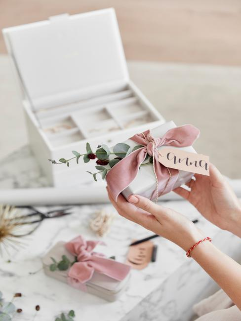 Białe pudełko na kosmetyki oraz pudełko prezentowe opakowane z różową kokardę i gałązkę eukaliptusa