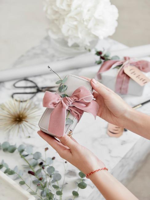 Szary portfel obwiązany różową wstążką i przełożony gałązką eukaliptusa
