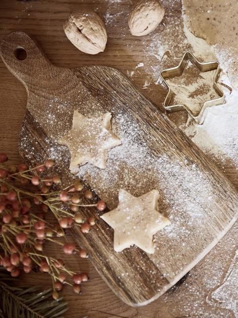 Dwa ciasteczka orzechowe w kształcie gwiazdek na drewnianej desce do krojenia
