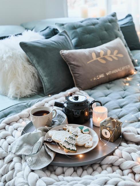 Łóżko z niebieską narzutą oraz tacą z miseczką z ciastkami, imbrykiem oraz kubkiem