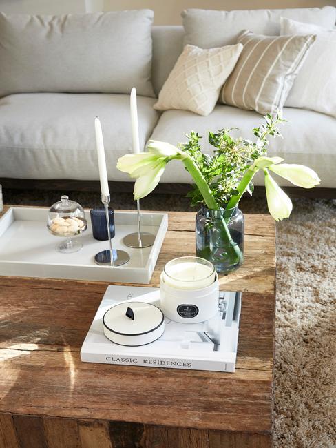 taca deckoracyjna z marmuru ze świecznikiem na drewnianym stoliku kawowym obok wazonu z białymi daliami