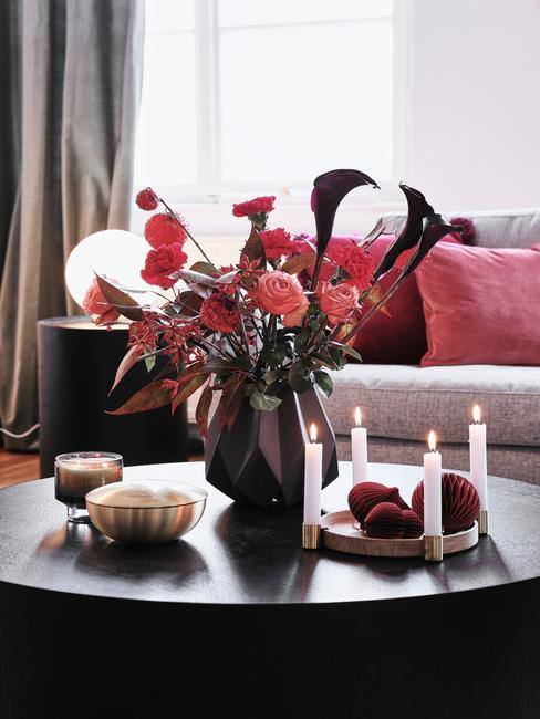 Zbliżenie na czarny wazon z bukietem, wieniec adwentowy oraz świeczki ustawione na czarnym stoliku kawowym