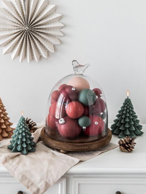 Bożonarodzeniowy stroik z czerwonych oraz zielonych bobmek postawiony na komodzie obok trzech świeczek