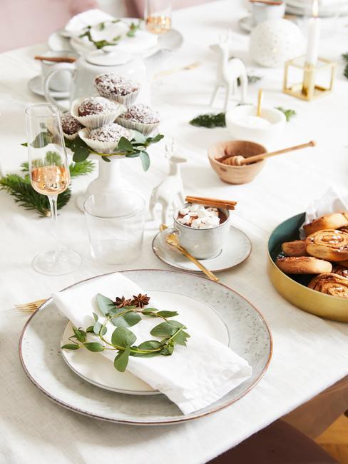 Biała dekoracja stołu wigilijnego z małym wieńcem na serwetce