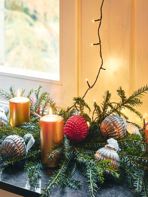 Fragment świerkowaej girlandy z świeczkami, bombkami oraz lampkami choinkowymi