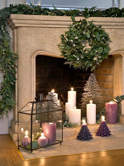Świąteczna dekoracja kominika w salonie przy wykorzystaniu wieńca, girlandy oraz świeczek i latarenek