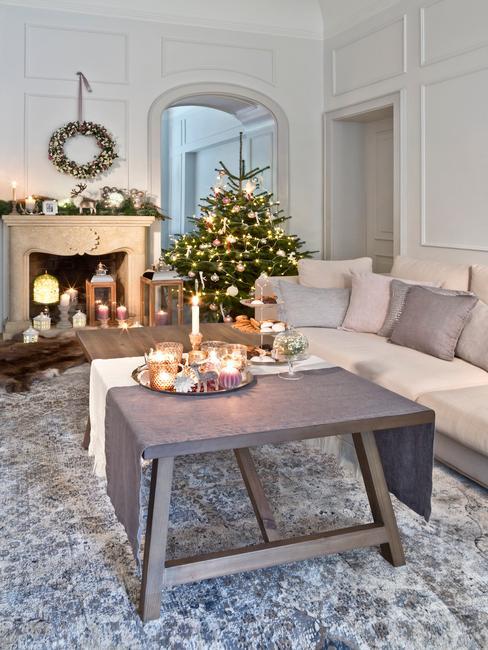Salon w stylu nowojorskim w jasną sofą, stolikiem kawowym, udekorowanym kominkiem i choinką