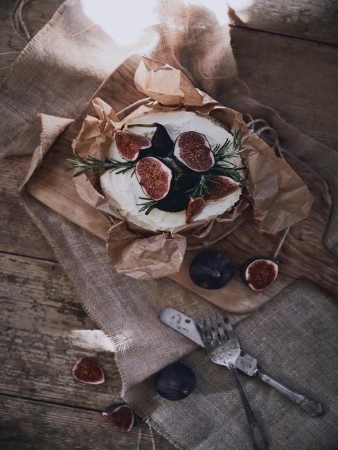 Drewniana deska z owniętym w papier serem pleśniowym, figami i rozmarynem