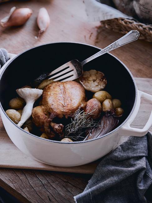 Pieczony kurczak z warzywami w garnku żeliwnym na drewnianym blacie