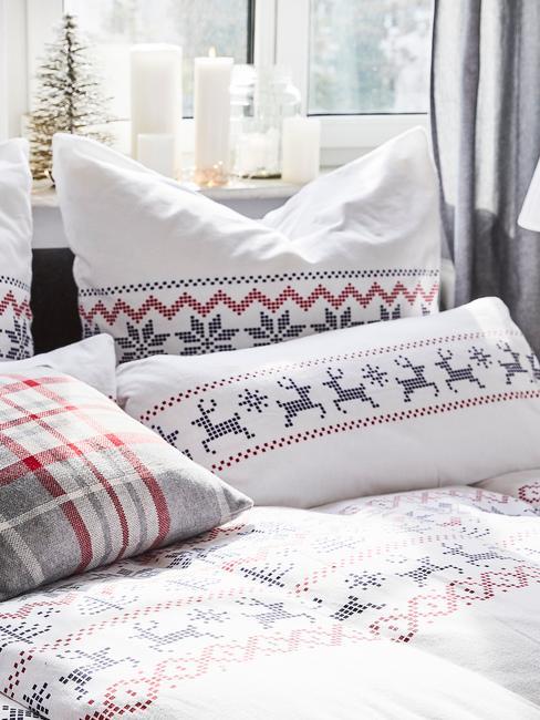 Sypialnia z łożkiem z pościelą świąteczną, parapetem ze świeczkami i małą choinką