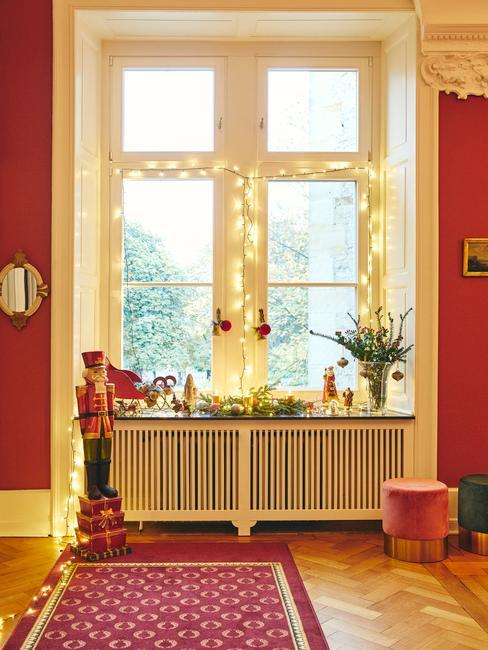 Zbliżenie na okno w pomieszczeniu ze światełkami, świątecznym bukietem oraz stroikiem bożonarodzeniowym