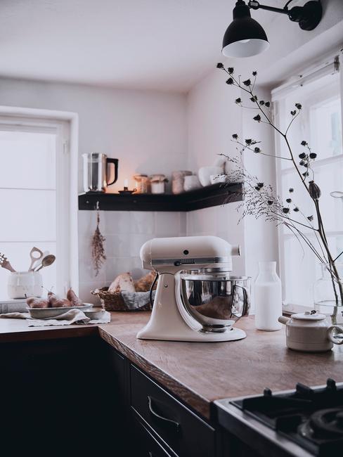 Biała kuchnia z drewnianym blatem, robotem kuchennym oraz suszoną gałęznią w wazonie