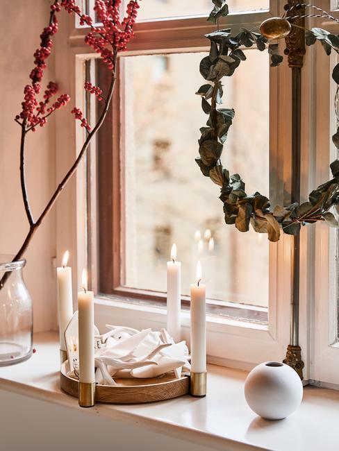Zbliżenie na świąteczną dekorację okna z wieńcem adwentowym z świeczkami oraz wiankiem z eukaliptusa powieszonym na oknie