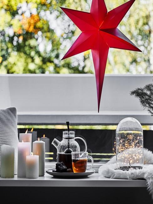 Udekorowany parapet za pomocą świec, dzbanka herbaty, lampy w kształcie gwiazy oraz latarenki