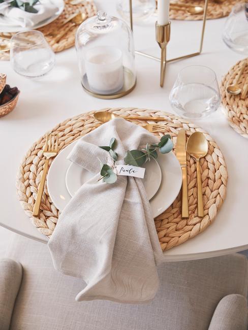 Zbliżenia na stół z białym obrusem, plecioną podstawką, białą zastawą, złotymi sztućcami i serwetką
