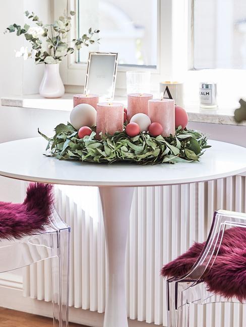 wieniec adwentowy z liści, na którym są różowe świece i bombki na białym okrągłym stole przy oknie