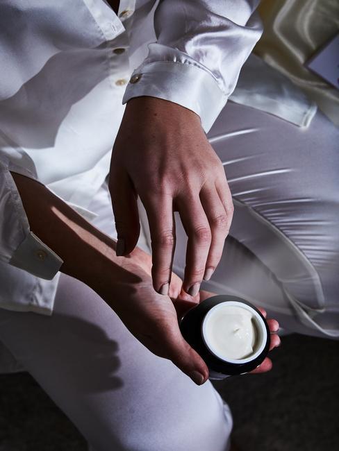 Osoba siedząca na skraju łóżka z jedwabnej piżamie wcierająca krem na skórę rąk