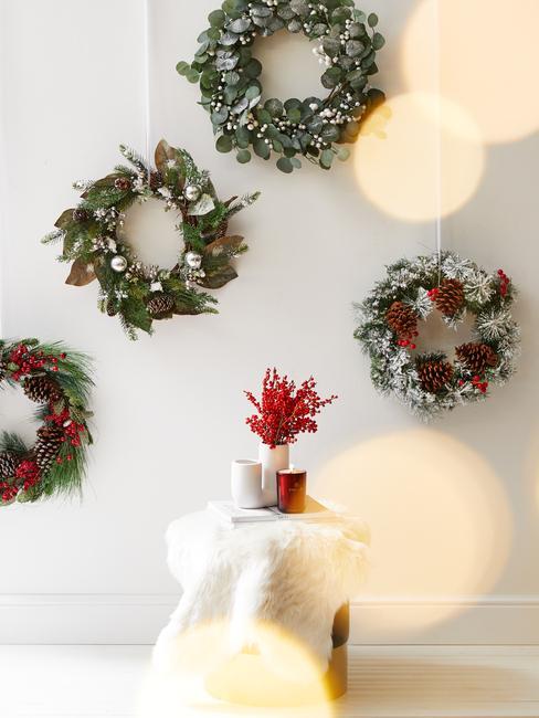 Cztery różne wieńce na białej ścianie nad stolikiem z wazonem z bukietem