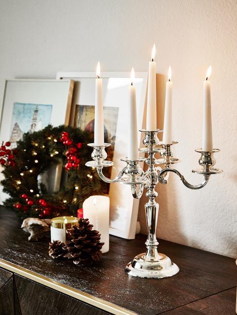 Dekoracja półki nad kominkiem ze srebrnym świecznikiem oraz wieńcem adwentowym