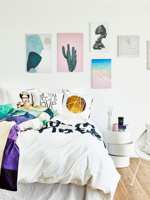 Biała sypialnia z kolorowymi dekoracjami w postaci obrazów na ścianie oraz poduszek dekoracyjnych