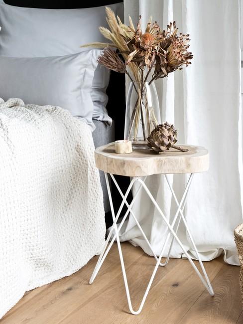 mały stolik nocny z drewnianym blatem na białych nóżkach z wazonem z suszonymi kwiatami obok jasnego łóżka