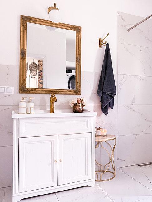 Łazienka z białymi meblami i złotymi dekoracjami w stylu glamour