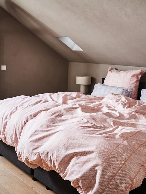 Sypialnia na poddaszu z dużym łożkiem z różową pościelą