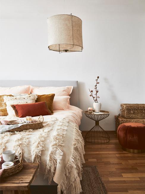 Sypialnia w stylu etno z kocem, kolorowymi poduszkami oraz stoliczkiem nocnym z rośliną