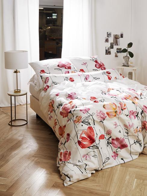 Biała sypialnia z drewnianą podłogą i pościelą w kwiaty