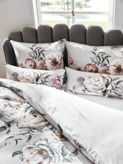 Zbliżenie na łóżko z szarym zagłówkiem oraz pościelą w kwiaty