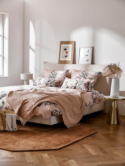 Biała sypialnia w dużym łóżkiem, jutowym dywanem oraz stolikami nocnymi