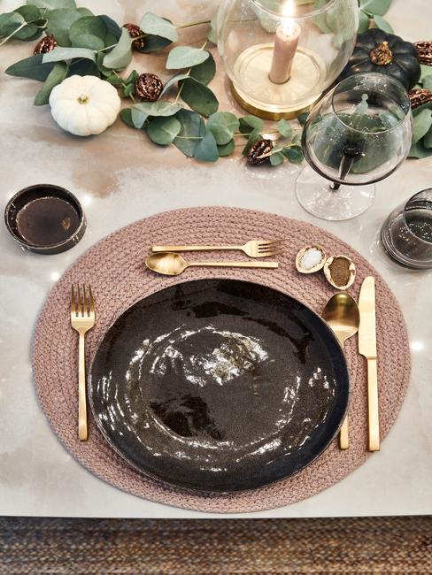 Udekorowany stół girladną z eukaliptusa i białymi dyniami, czarną zastawą i złotymi sztućami