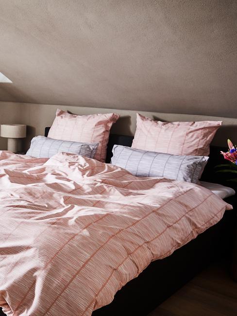 Sypialnia na poddaszu z łóżkiem z różową pościelą