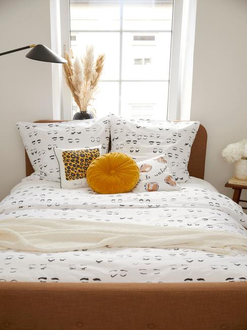 Mała sypialnia w łóżkiem z kolorową pościelą, poduszkami, lampaki oraz stoliczkiem z kwiatami