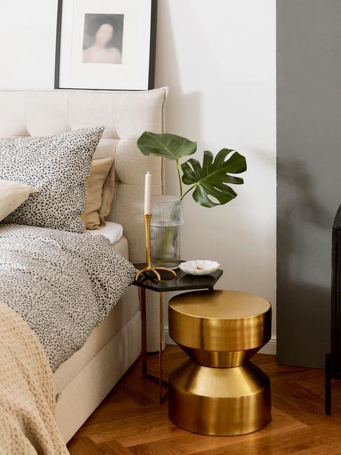 Zbliżenie na fregment sypialnia ze stoliczkiem nocnym z rośliną oraz złotym stołkiem