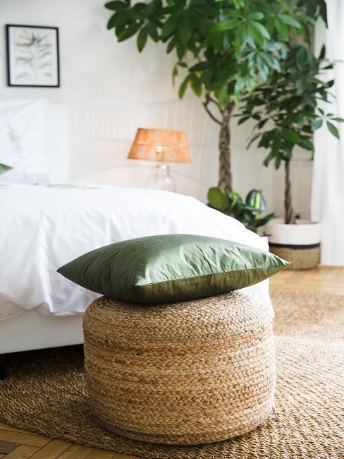 Zbliżenie na jutowy puf z zieloną poduszką w białej sypialni
