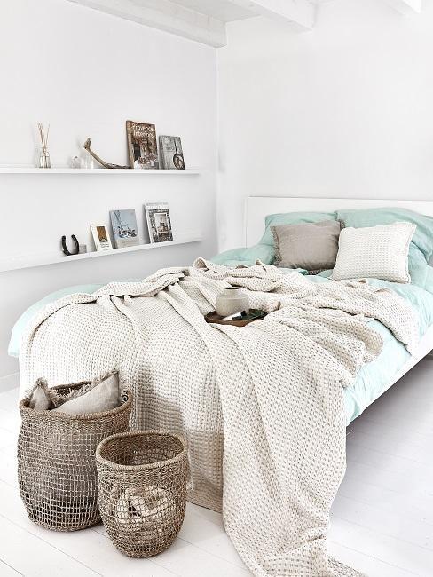 Biała sypialnia z łożkiem o błękitnej pościeli z poduszkami oraz dekoracjami w pomieszczeniu